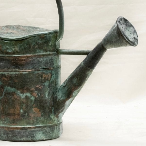 Close up of large antique copper watering can with a natural antique patina.
