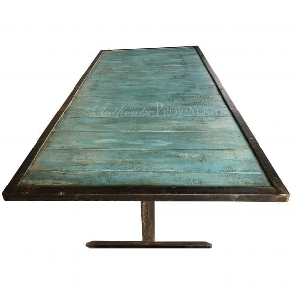 Overhead view of a rectangular wooden dining table painted turquoise with an iron base