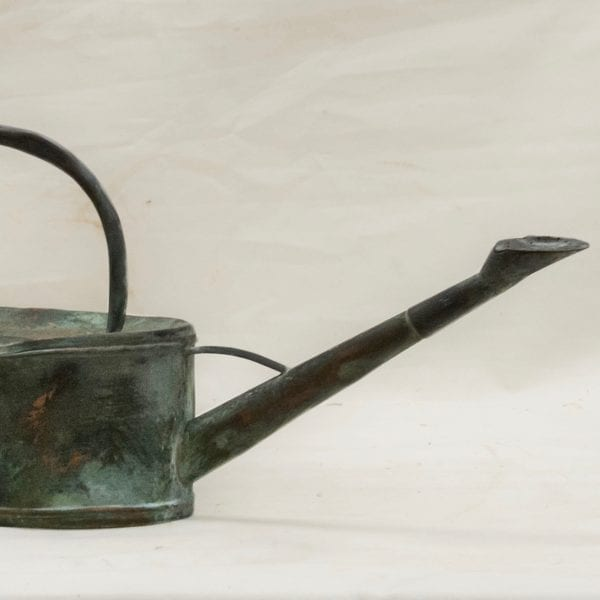 Close up of rustic copper antique water can with a large fine handle and natural antique patina.