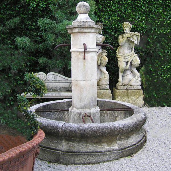 A traditional Provencal fountain with four metal tresses and octagonal beveled raised column with four traditional French metal spigots