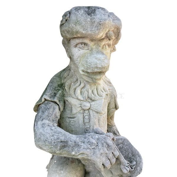 Close up of a limestone monkey statue with a painters palette dressed in typical basque hat