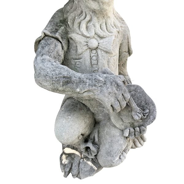 Close up of a limestone monkey statue with a painters palette