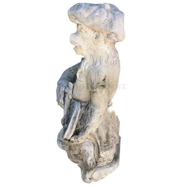 Side view of a limestone monkey statue carrying a painters palette dressed with typical basque hat.