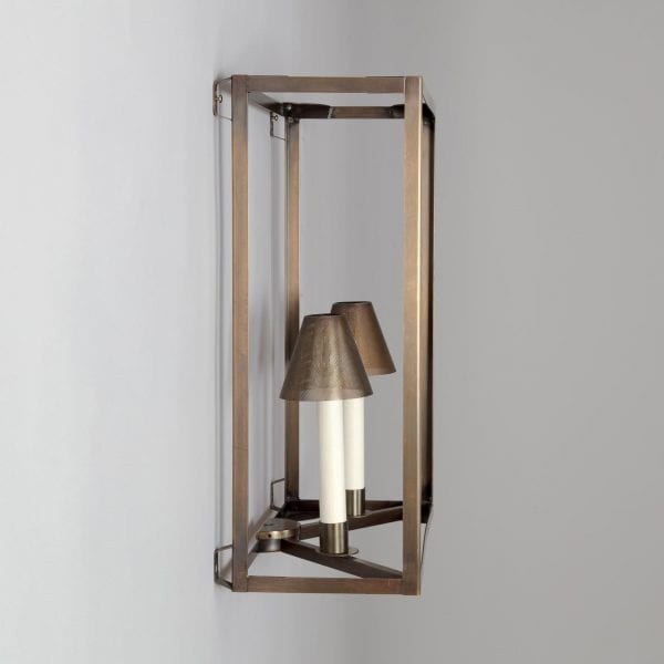 Side view of a minimalist interior light fixture. Wall mounted in brass with an antique finish and two perforated lamp shades.