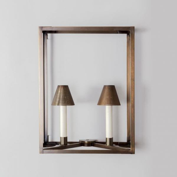 A minimalist interior light fixture. Wall mounted in brass with an antique finish and two perforated lamp shades.