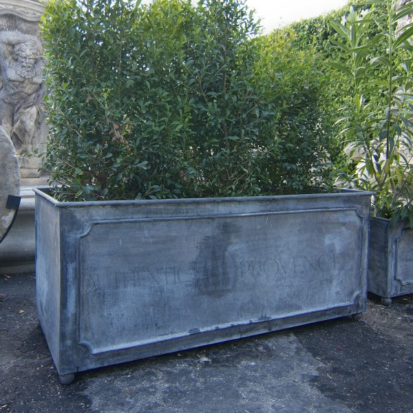 A large rectangular garden planter in galvanized metal with a lead finish filled with greenery