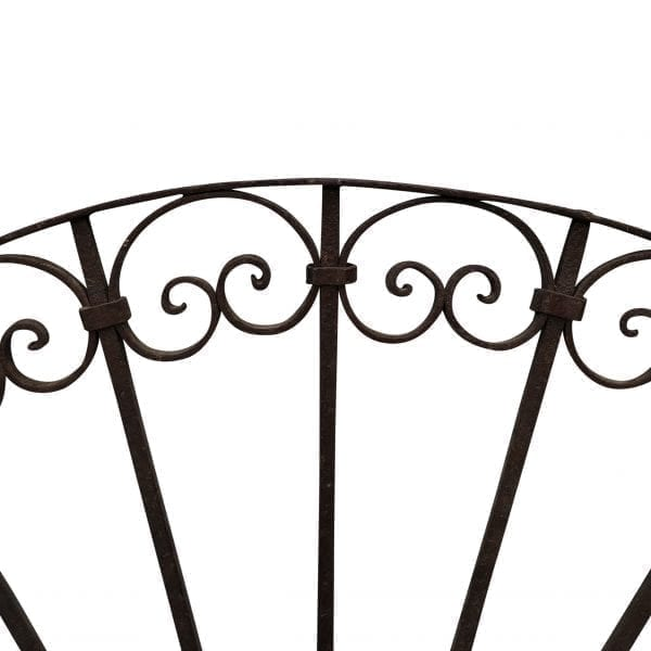 Close up of the top arch of a antique demi lune wrought iron gate insert