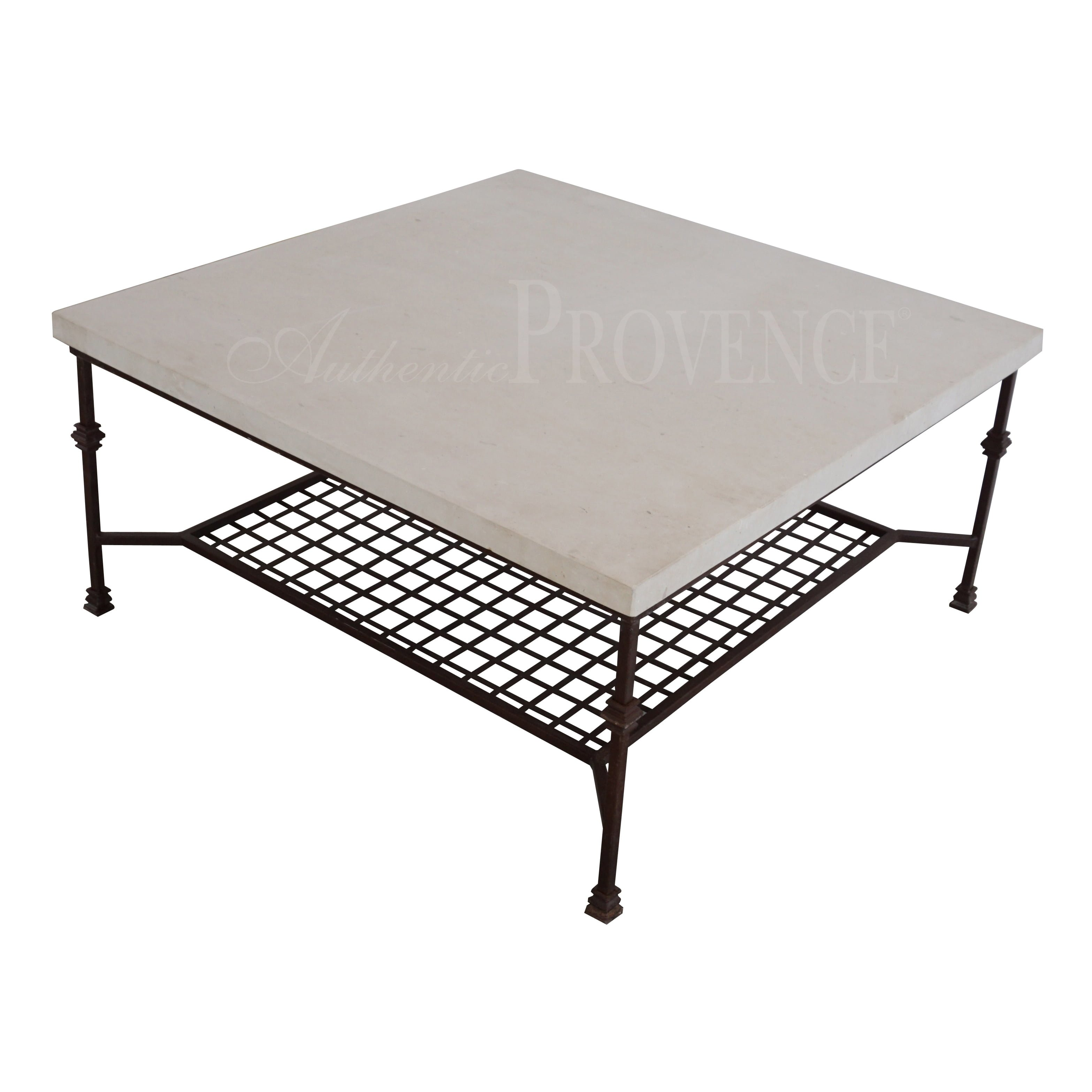 A coffee table with square French limestone top on an iron base with grid
