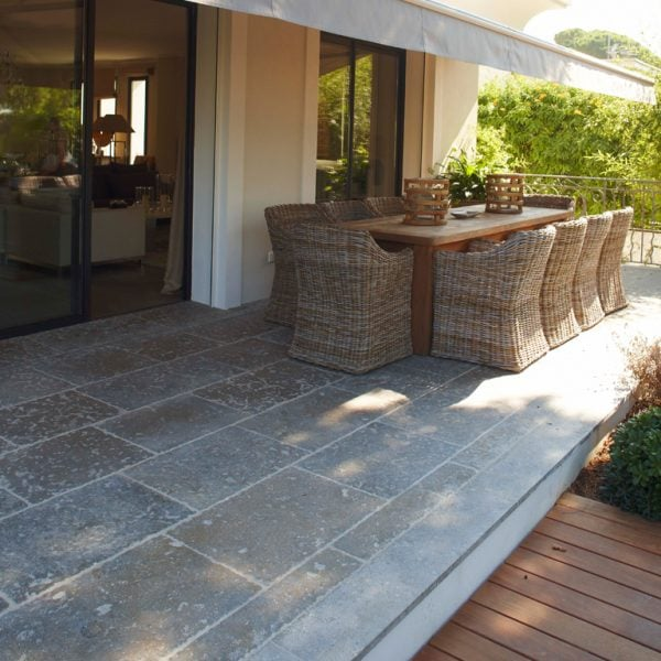 A refined blue grey to taupe dense colored limestone floor with a smooth surface and fine grain in an outdoor setting
