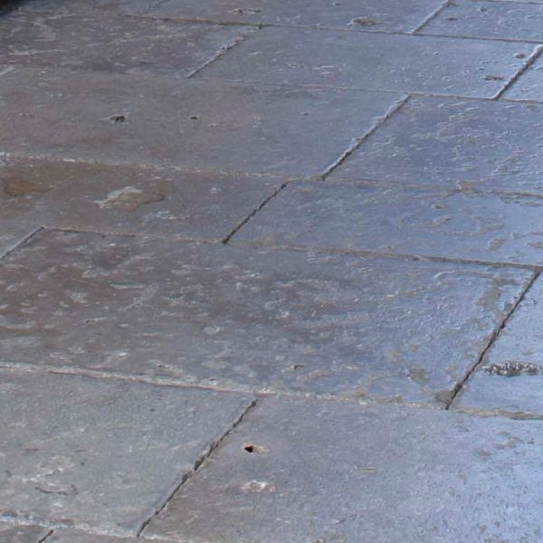 Close up of a refined blue grey to taupe dense colored limestone floor with a smooth surface and fine grain