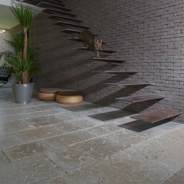 A refined blue grey to taupe dense colored limestone floor with a smooth surface and fine grain in an indoor setting