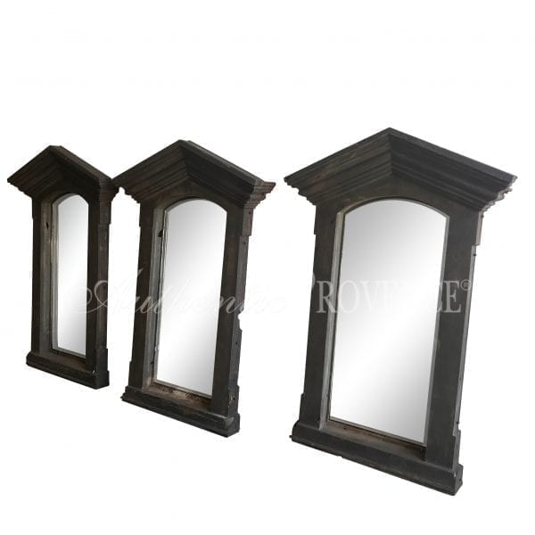A set of three industrial cast iron frames in the Neoclassical taste with antiqued glass mirrors.