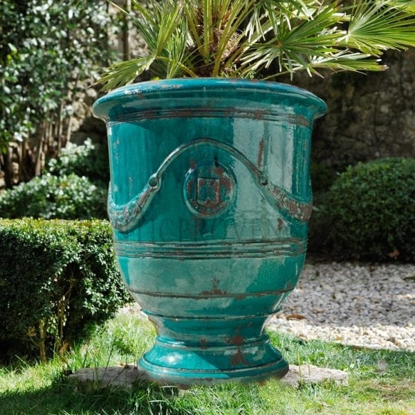Partially glazed turquoise Anduze garden planter with an antiqued patina and adorned with swags and an emblem.