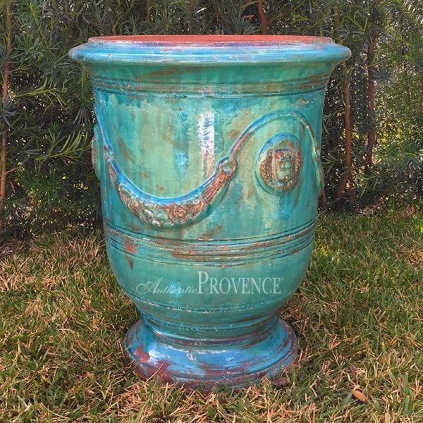 Handmade partially glazed turquoise Anduze garden planter with an antiqued patina and adorned with swags and an emblem.