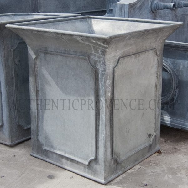 A large paneled border garden planter in galvanized metal with beveled panels and tulip shaped border rim.