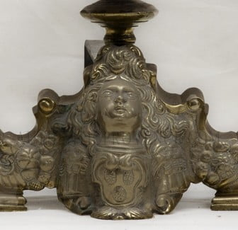 French 19th century andiron capped witha decorative brass finial and female face.