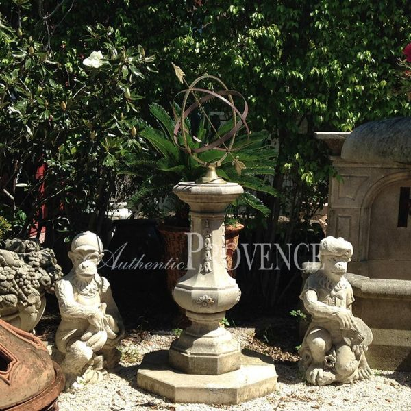 An armillary sphere made of brass with limestone baluster pedestal decorated with foliage and raised upon an octagonal platform