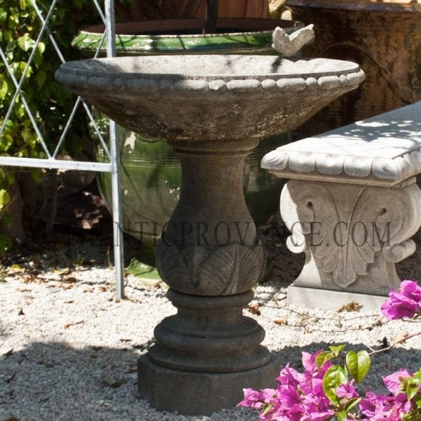 Round bird bath decorated with acanthus foliage and a small bird decoration
