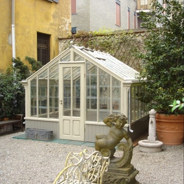 An antique architectural garden conservatory with recently added hardware and gutters.