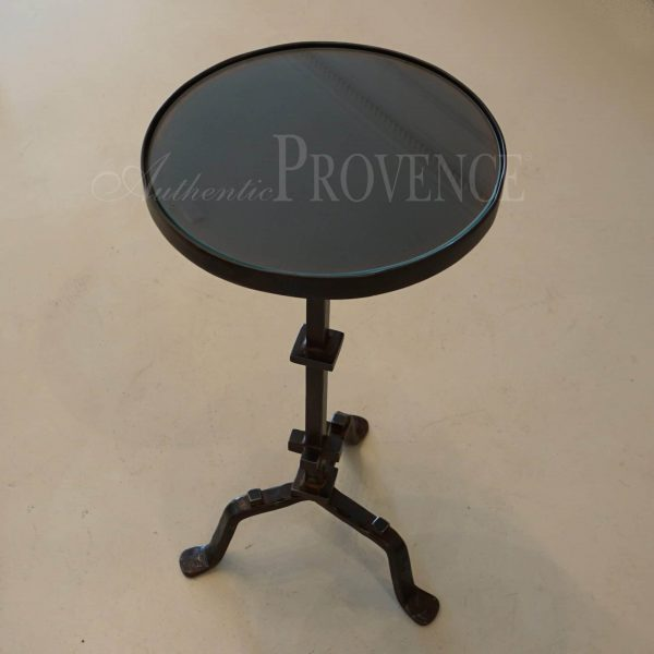 A very petite round side table with hand forged metal base and glass inset top from France