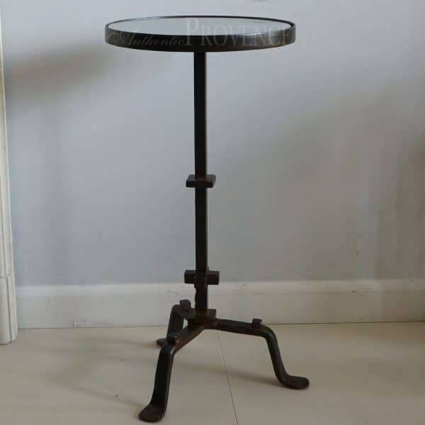Side view of a small round table with hand forged metal base and glass inset top