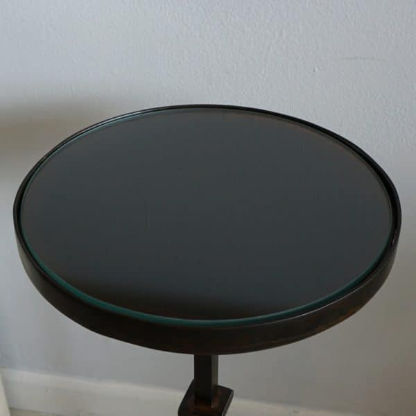 Overhead view of a small round table with glass inset top and metal base