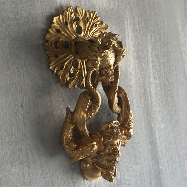 Side view of an door knocker of Neptune and dolphins in a Renaissance style with a round back plate and a ring