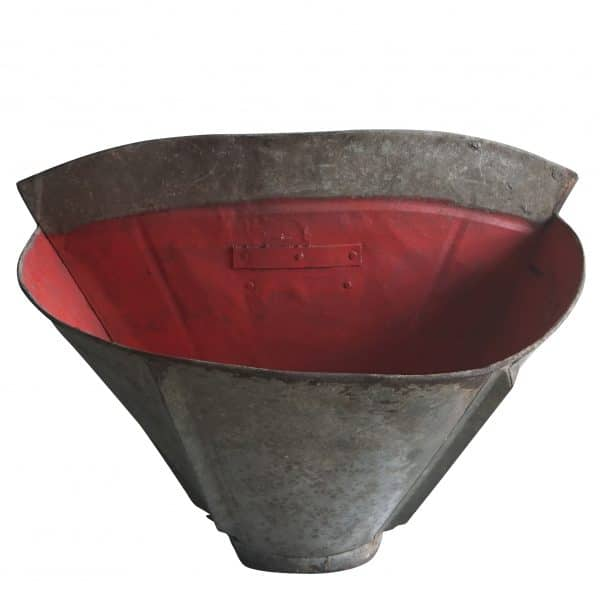 An antique French grape carrier in galvanized metal with red detailing inside.