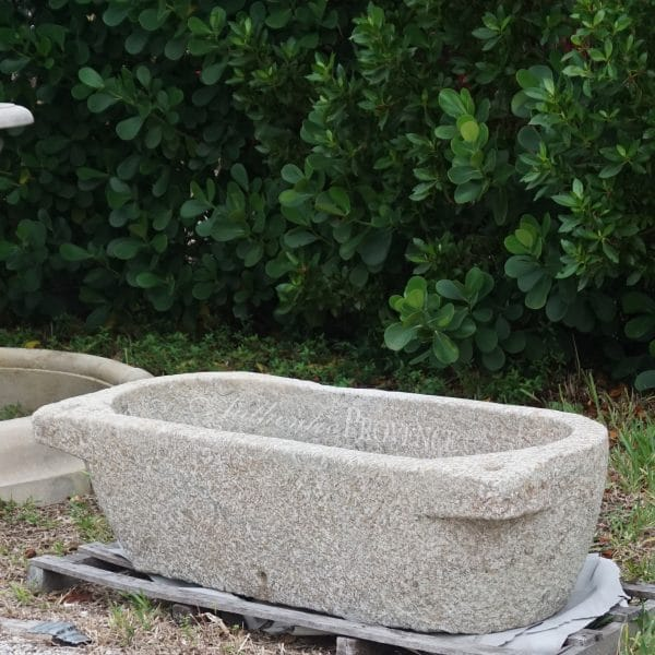 Side view of large mid 19th Century tapered trough basin made of granite with protruding laterals