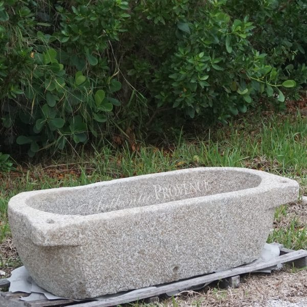 A large tapered granite trough basin with protruding laterals