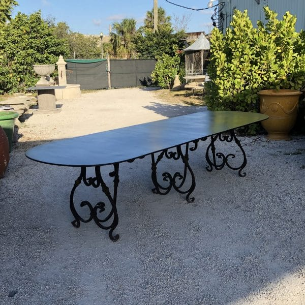 Side view of a large oval shaped table in iron with adark brown finish andscroll base in an outdoor setting