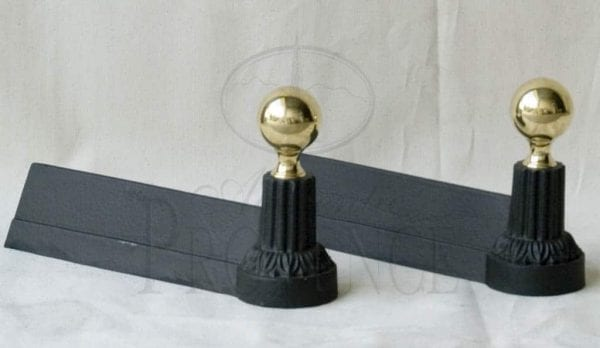 A pair of small cast iron andirons or fire dogs with matte black patina and brass spheres