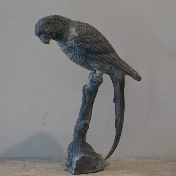 Side view of a lead garden ornament of a Parrot perched on a branch