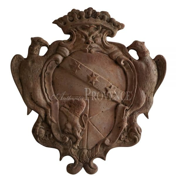 Heavily ornate Tuscan terra cotta clay shield with eagles flanking the oval shaped coat of arms and topped with a crown