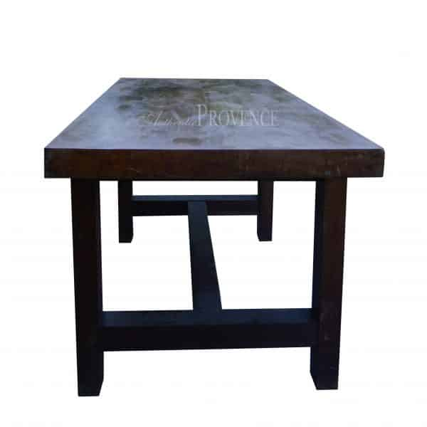 Side view of French conference table with four legs and a centered base foot rest made of walnut