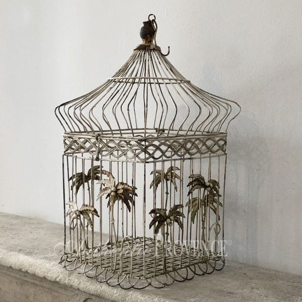 Side view of vintage wire work bird cage with palm tree decor from the Victorian period in good condition.