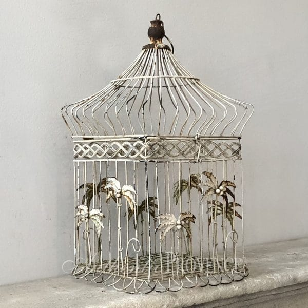 Side view of vintage wire work bird cage with palm tree decor from the Victorian period