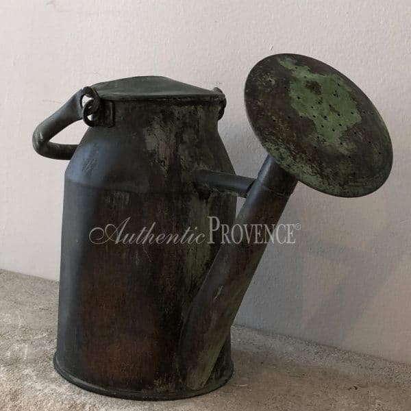 Close up of a large antique copper watering can with a natural antique patina and double handles