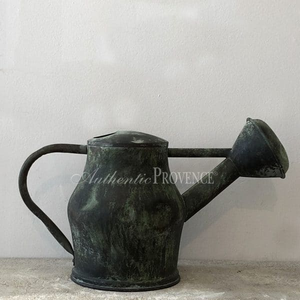 A large antique copper watering can with a natural antique patina