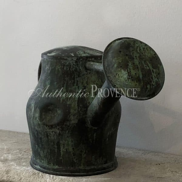 Close up of large antique copper watering can with a natural antique patina