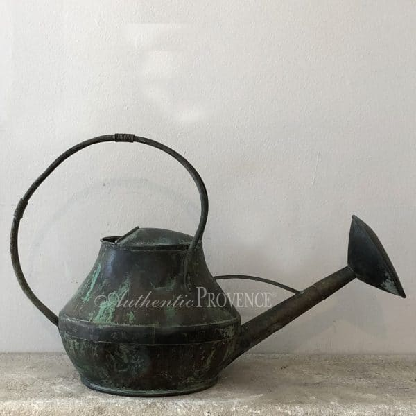 A large antique watering can with a fine curved handle. This copper watering can has a natural antique patina.