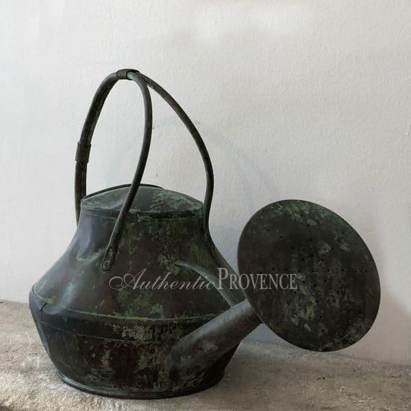 Close up of large antique watering can with a fine curved handle. This copper watering can has a natural antique patina.