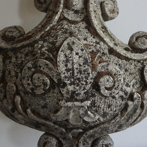 Close up of Fleur de lys crest with an aged mossy surface