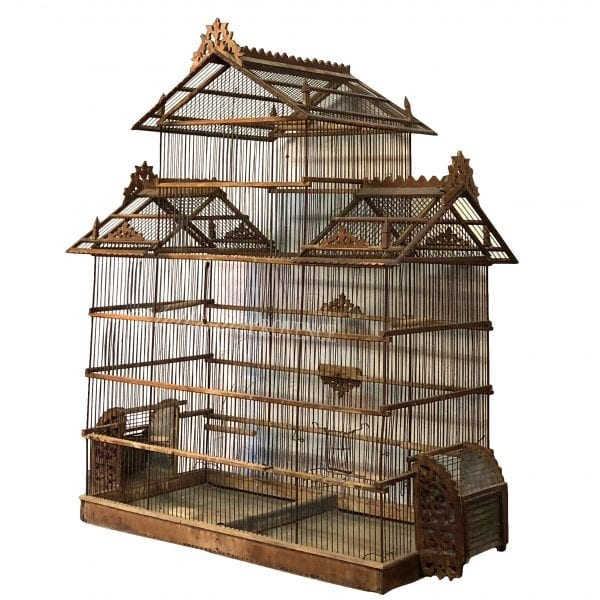 Side view of antique French wire birdcage in pagoda shape made of walnut. The roof is decorated with filigree tracery carving in good condition.