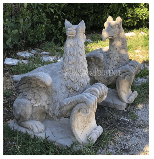 A side view of a stunning pair of opposing seated griffins made of hand carved limestone on bases from a Venetian estate.