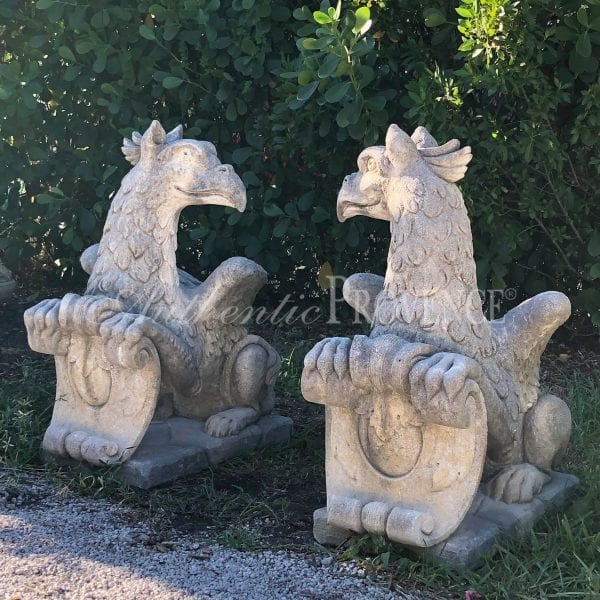 A stunning pair of opposing seated griffins made of hand carved limestone on bases from a Venetian estate
