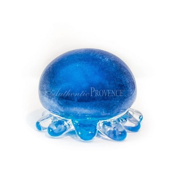 Blue glass paperweight in shape of a jelly fish with small curved arms.
