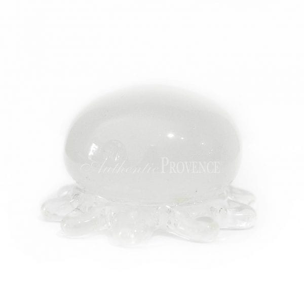 White glass paperweight in shape of a jelly fish with small curved arms.