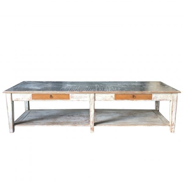 A large rectangular garden table with rustic galvanized metal top and wooden base with two faux drawers and bottom shelf