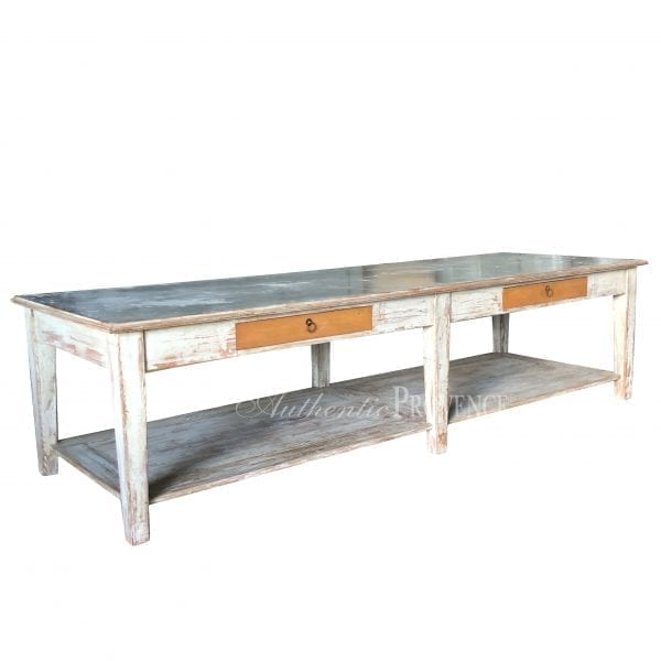 Side view of a large rectangular garden table with rustic galvanized metal top and wooden base with two faux drawers and bottom shelf